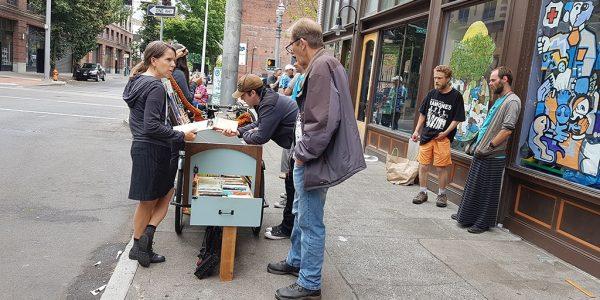 Laura Moulton (li) und Ben Hodgson am Streetbooks-Stand vor Sisters of the Road mit Kunden